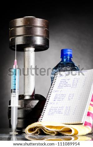sport stimulants. metal barbells with syringe - stock photo