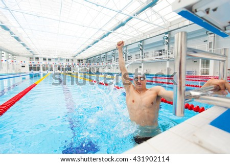 Sport swimmer winning. Man swimming cheering celebrating victory success smiling happy in pool wearing swim goggles and gray cap. - stock photo