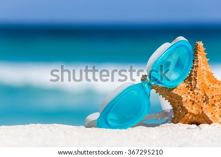 Sport swimming glasses and starfish on white sand against turquoise caribbean sea water. Tropical summer vacation concept