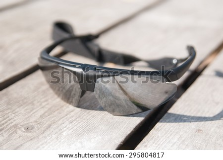 Sport (tactical) glasses on a wooden base. reflecting surface