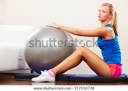 Sport, training, gym and lifestyle concept. Young attractive slim woman in sportwear doing fitness exercises with fit ball at home