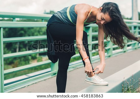 Sport woman city summer.Close-up of beautiful young woman in sports clothing tying her shoelaces on bridge.