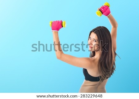 Sport woman doing weightlifting over colorful background