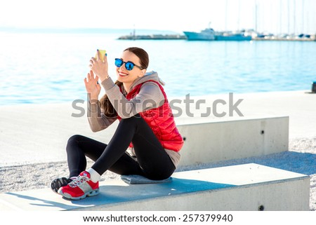 Sport woman dressed in warm clothes resting with phone and headphones after the exercise on the promenade in Spring - stock photo