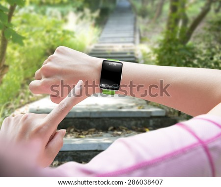 Sport woman finger pointing smart watch with blank black glass bent touchscreen, on forest trail background