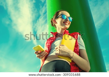 Sport woman in red vest using smart phone near the green lighthouse on the blue sky background. Photo with cross processing filter - stock photo