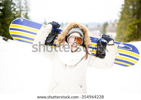 Sport woman in snowy mountains. The concept of the winter holiday. Snowboarding.Young beautiful woman with ski mask holding her snowboard at ski slope Young woman holding snowboard on her shoulders - stock photo