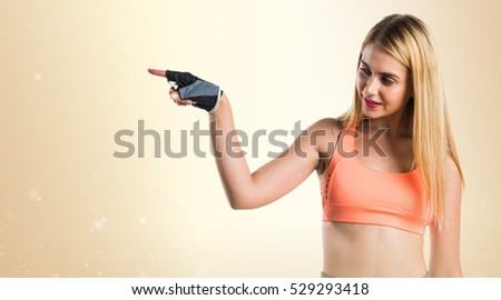 Sport woman pointing to the lateral on ocher background