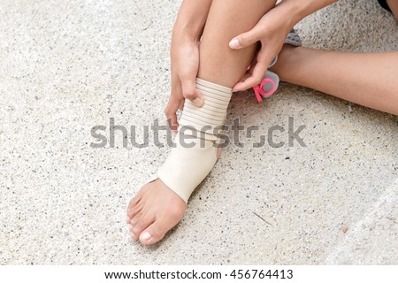 sport woman runner hurting holding painful sprained ankle in pain with blur background.