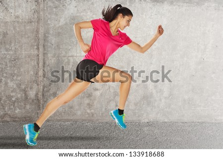 Sport woman starting running. young woman jogging front cement wall - stock photo