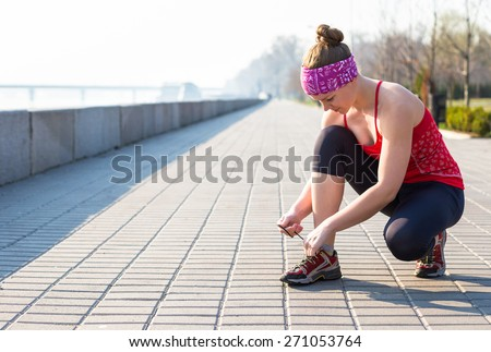 Sport woman tying running shoes during training in park in the morning - stock photo
