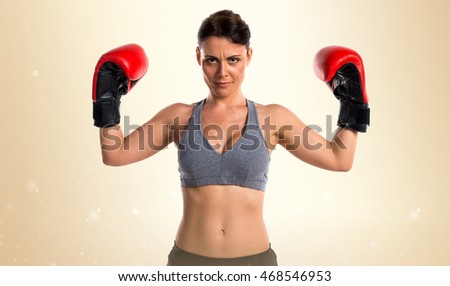Sport woman with boxing gloves over ocher background