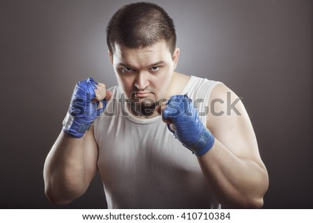 Sport. Young athletic man before the fight or training. Muscular and strong guy exercising.