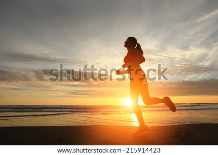Sport young woman running on the beach at sunrise, asian