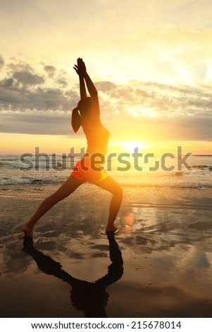 Sport Young woman silhouette practicing yoga on the sea beach at sunset