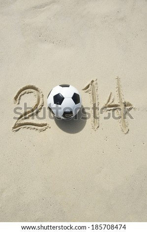 Sporting message for 2014 made with football soccer ball on bright sunny beach in Rio - stock photo