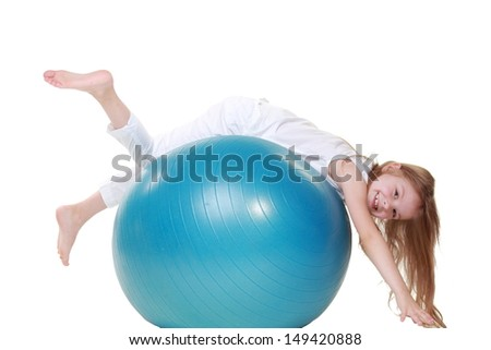 Sporting young girl jumping on a fitball and smiling on a white background