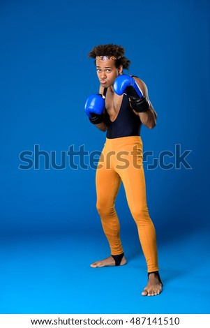 Sportive african man in boxing gloves training over blue background.
