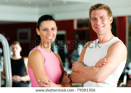 Sportive couple in gym or fitness club looking at the viewer