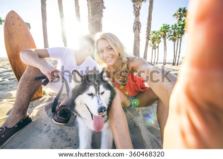 Sportive couple with husky taking a selfie with smartphone - Two friends smilingand having fun while resting in the shadow of palm trees on a tropical beach - stock photo