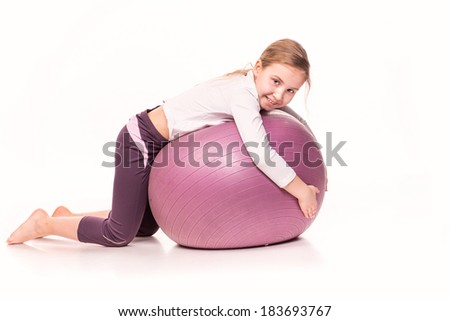 Sportive cute little girl on a fit ball isolated over white