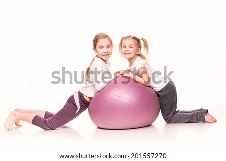 Sportive cute little girls on a fit ball isolated over white - stock photo