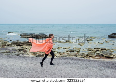 Sportive girl is running in the rainy morning outdoors.Young female runner is jogging along seashore.Picture attracts with fresh air and mild weather.Fit women working out outside with copy space area - stock photo
