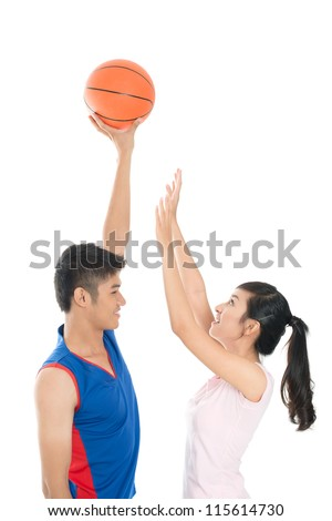Sportive girl reaching to the ball held by her cheerful friend - stock photo