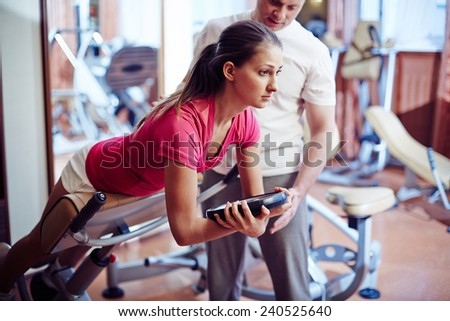 Sportive girl training in gym with her trainer near by - stock photo