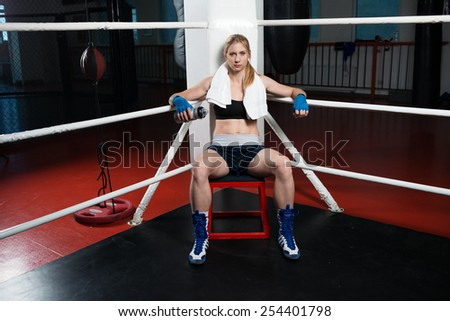 Sportive girl with blond hair in sport clothes and boxer gloves posing on ring - stock photo