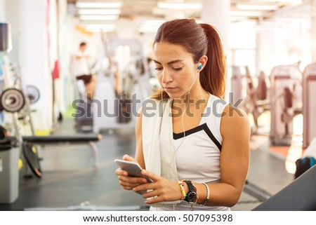 Sportive girl with earphones and smartphone in fitness gym.