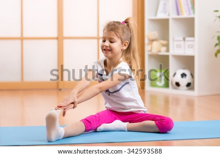 Sportive kid girl doing gymnastic at home - stock photo