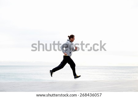 Sportive male runner working out outdoors jogging along seashore with beautiful sky horizon on background, jogger listening to music on smart phone while training outdoors