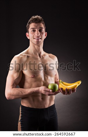Sportive man holds fruits against dark background
