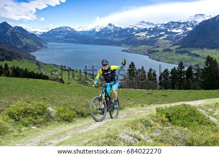 Sportive man in middle age with mountain bike on mountain trail beckons the viewer. The background shows the Lake Lucerne.