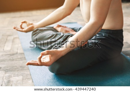 Sportive man's body wearing trousers doing yoga position and sitting on blue matt, position of fingers in mudra, copy space, portrait, lotus asana. - stock photo