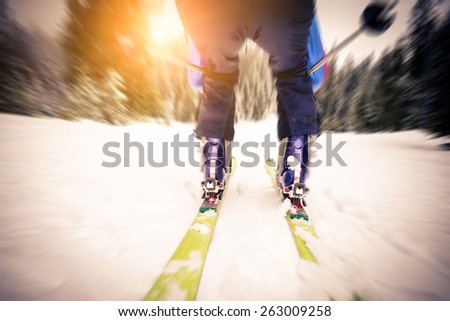 Sportive man skiing on a mountain - Skier leaning down and skiing fast downhill at sunset with motion blur effect - stock photo