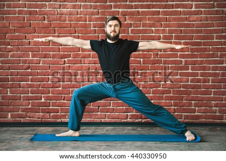 Sportive man with a beard wearing black T-shirt and blue trousers doing yoga warrior position on blue matt at wall background, copy space, virabhadrasana. - stock photo