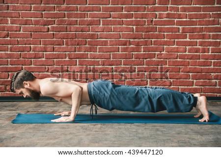 Sportive man with a beard wearing trousers doing yoga position on blue matt at wall background, copy space, portrait, chaturanga dandastana asana. - stock photo