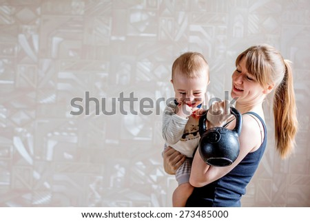 Sportive mother with cute baby and kettlebell in hands. Motherhood is not a cause to let oneself go - stock photo