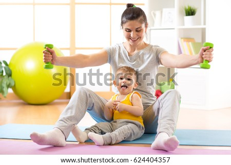 Sportive mother with little kid boy doing gymnastics and fitness exercises.