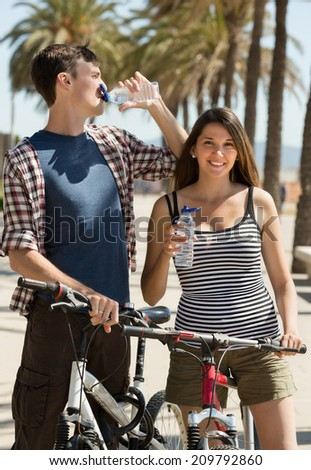Sportive  people with bikes resting and drinking still water - stock photo