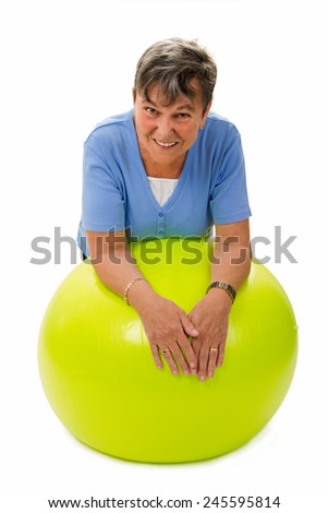 Sportive senior woman leaning on a fitness ball - stock photo