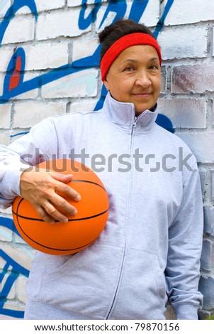 Sportive senior woman with a basketball - stock photo