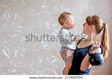Sportive smiling mother and baby and kettlebell in hands. Motherhood is not a cause to let oneself go - stock photo