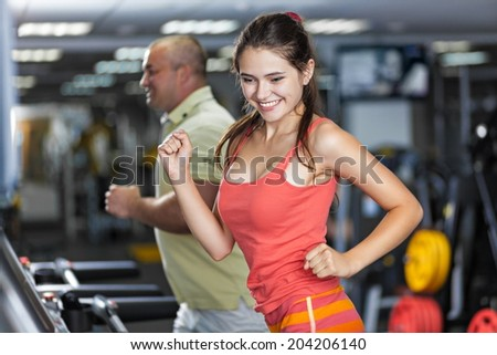 Sportive woman and man are running on treadmill in a gym - stock photo