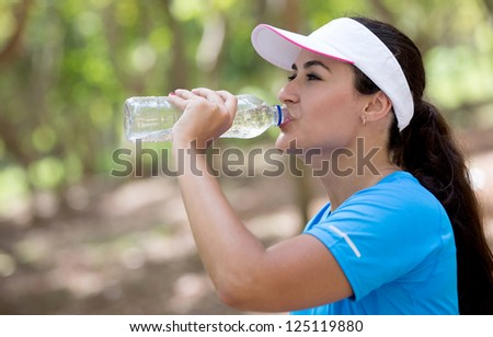 Sportive woman drinking water after her workout