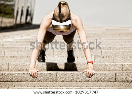 Sportive woman makes her pushup workout on stairs, wearing virtual reality glasses which show a nature scene and fitness data. A red fitness tracker is located on her left arm.