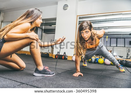 Sportive woman making pushups with one hand - Athlete training in a gym with coach - Girls working out in a fitness center - stock photo