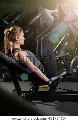 Sportive woman using weights press machine for legs at the gym. Pretty brunette exercising in a simulator. Working her quads at machine. - stock photo